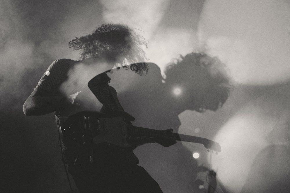 uomo suona la chitarra elettrica ad un concerto rock.