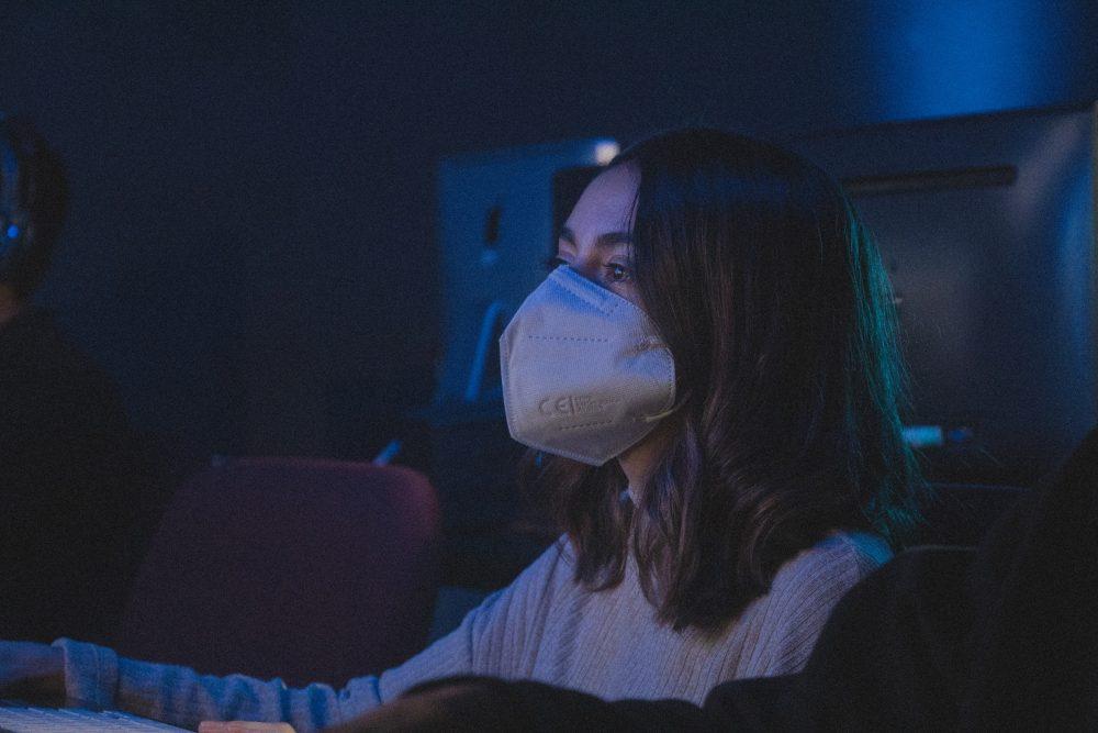 ragazza con mascherina in un teatro, guarda un evento dal vivo.