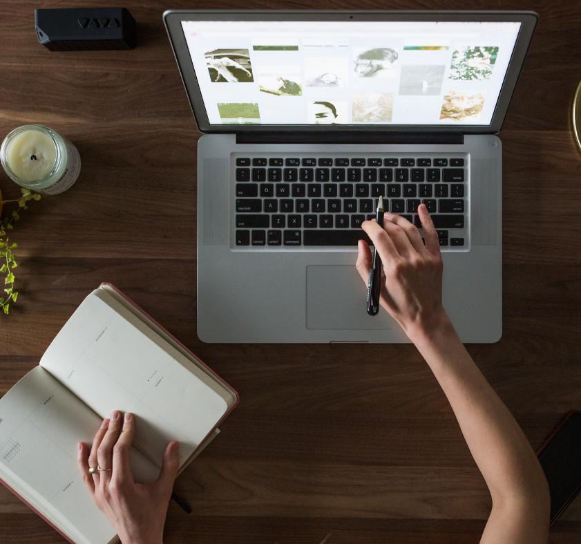 La mano di una ragazza mentre lavora al computer, posizionato su una scrivania. La ragazza tiene nella mano sinistra un'agenda.