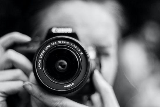 ragazza che tiene in mano una macchina fotografica