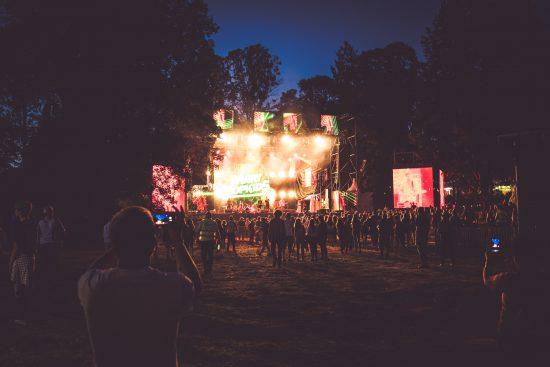 persone che si avvicinano ad un palco illuminato